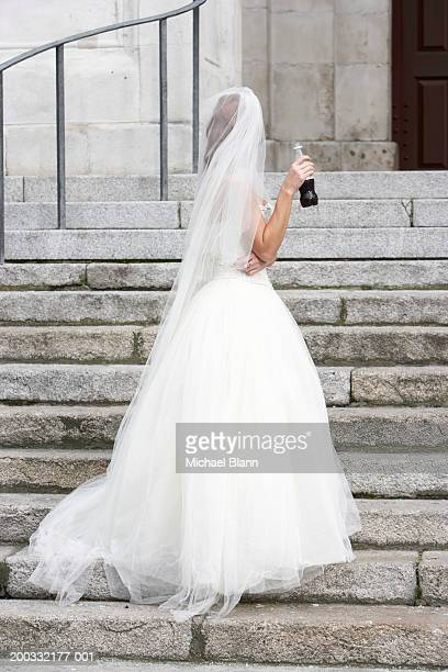 bride standing on steps to church, holding bottled drink, rear view - tulle netting stock pictures, royalty-free photos & images