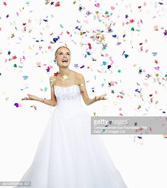 Bride standing under confetti, smiling