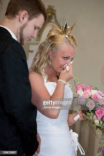 Bride standing with groom blowing her nose
