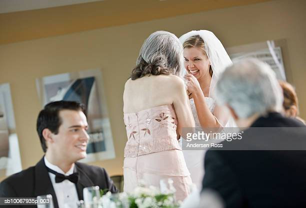 Bride talking with mother and groom with father during wedding party