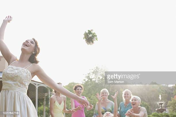 Bride throwing bouquet at wedding reception