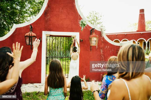 Bride throwing bouquet during outdoor wedding reception