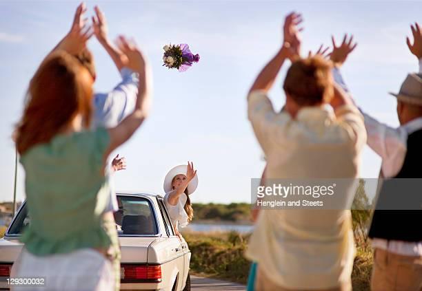 花嫁投げるブーケを車から