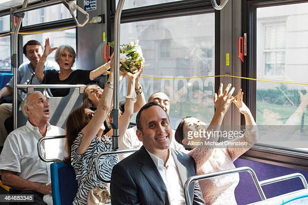 Bride throwing bouquet on city bus just married.