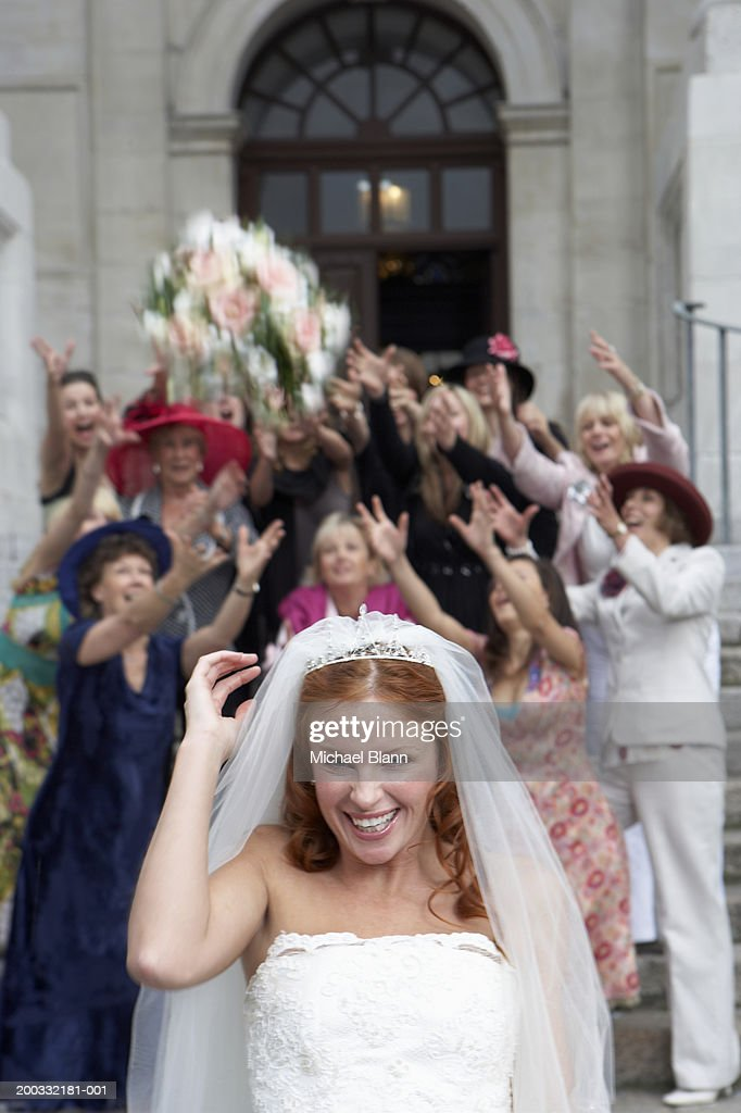 Bride throwing bouquet over head to crowd standing on steps to church : Stock Photo