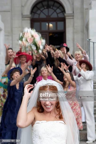 Braut werfen bouquet über Kopf nach Menschenmenge stehen
