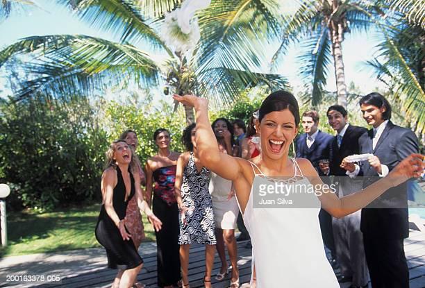 bride throwing wedding bouquet at outdoor reception - 投げる ストックフォトと画像