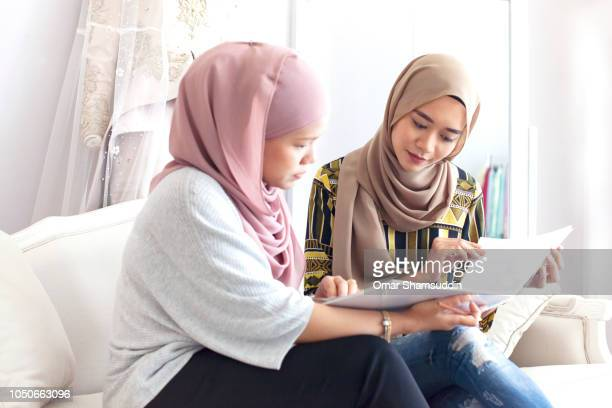 Bride to be browsing wedding dress design with the designer
