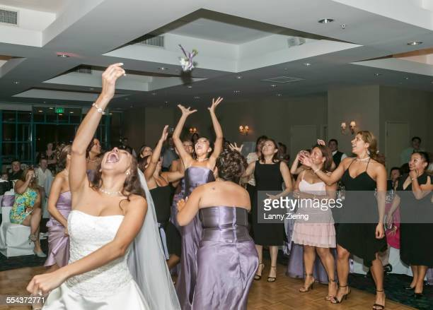 bride tossing bouquet to bridesmaids in wedding reception - ceremonia matrimonial fotografías e imágenes de stock