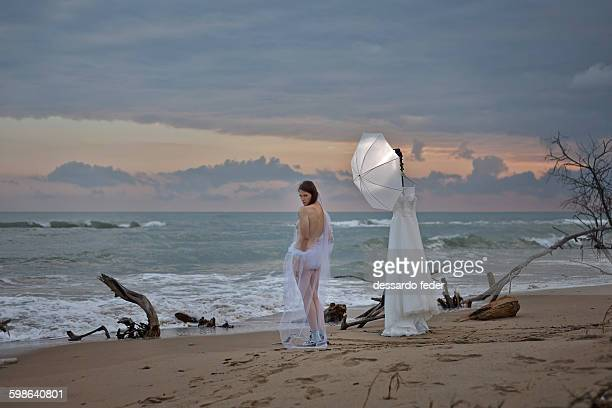 bride undressed waterfront - dressed undressed women stockfoto's en -beelden
