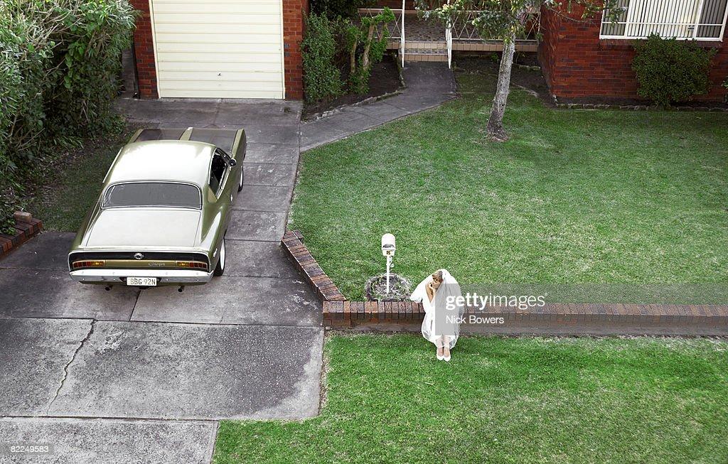Bride waiting alone on brick wall : Stock Photo