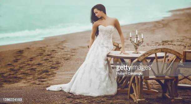 bride waiting for her husband in front of a wooden table with her wedding gown by the beach. - ceremony stock pictures, royalty-free photos & images