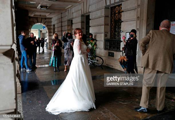 Bride waits to enter the City Hall in Nottingham, central England on October 29, 2020 as the city prepares to be moved into the UK government's...