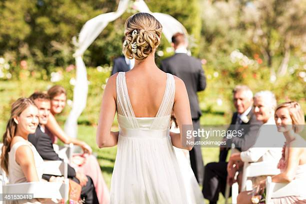 bride walking down the aisle during wedding ceremony - ceremony stock pictures, royalty-free photos & images