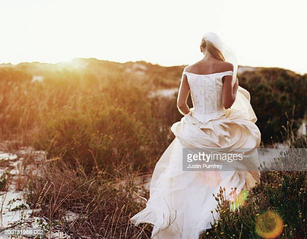 Bride walking through grassy sand dunes, rear view