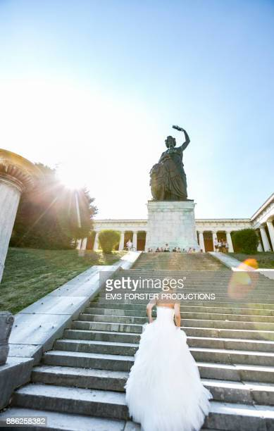 bride walking up the steps to Munich's Bavaria statue after wedding ceremony in her wedding dress