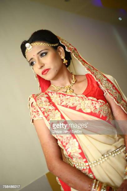 Bride Wearing Sari Looking Away While Standing Against Wall At Home