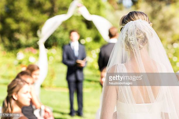 bride wearing veil walking down the aisle during garden wedding - veil stock pictures, royalty-free photos & images