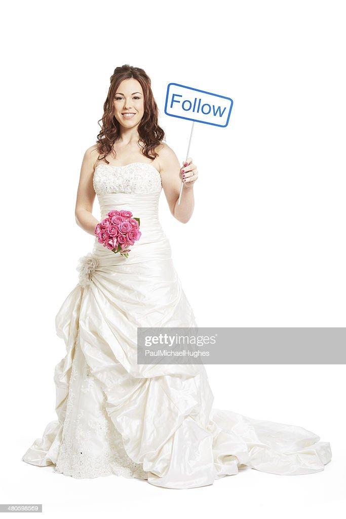 Bride wearing wedding dress holding a social media sign : Stock Photo
