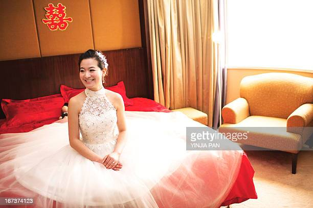 Bride wearing wedding dress sitting on bed