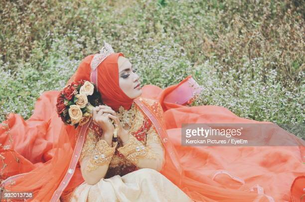 bride wearing wedding dress while sitting on grassy field at park - orange dress stock pictures, royalty-free photos & images