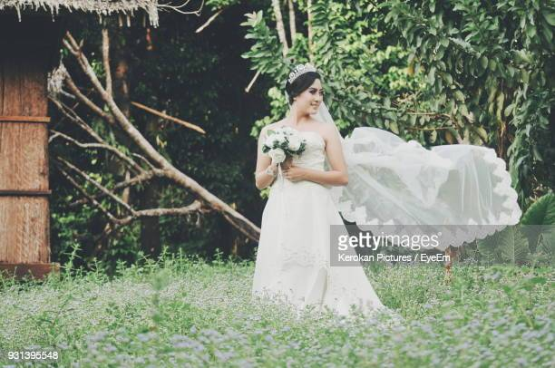 Bride Wearing Wedding Dress While Standing On Grassy Field At Park