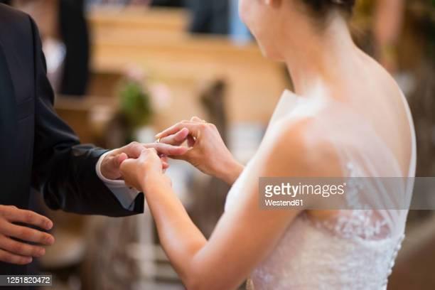 bride wearing wedding ring to bridegroom while standing in church -  キリスト教 伝来の地  ストックフォトと画像