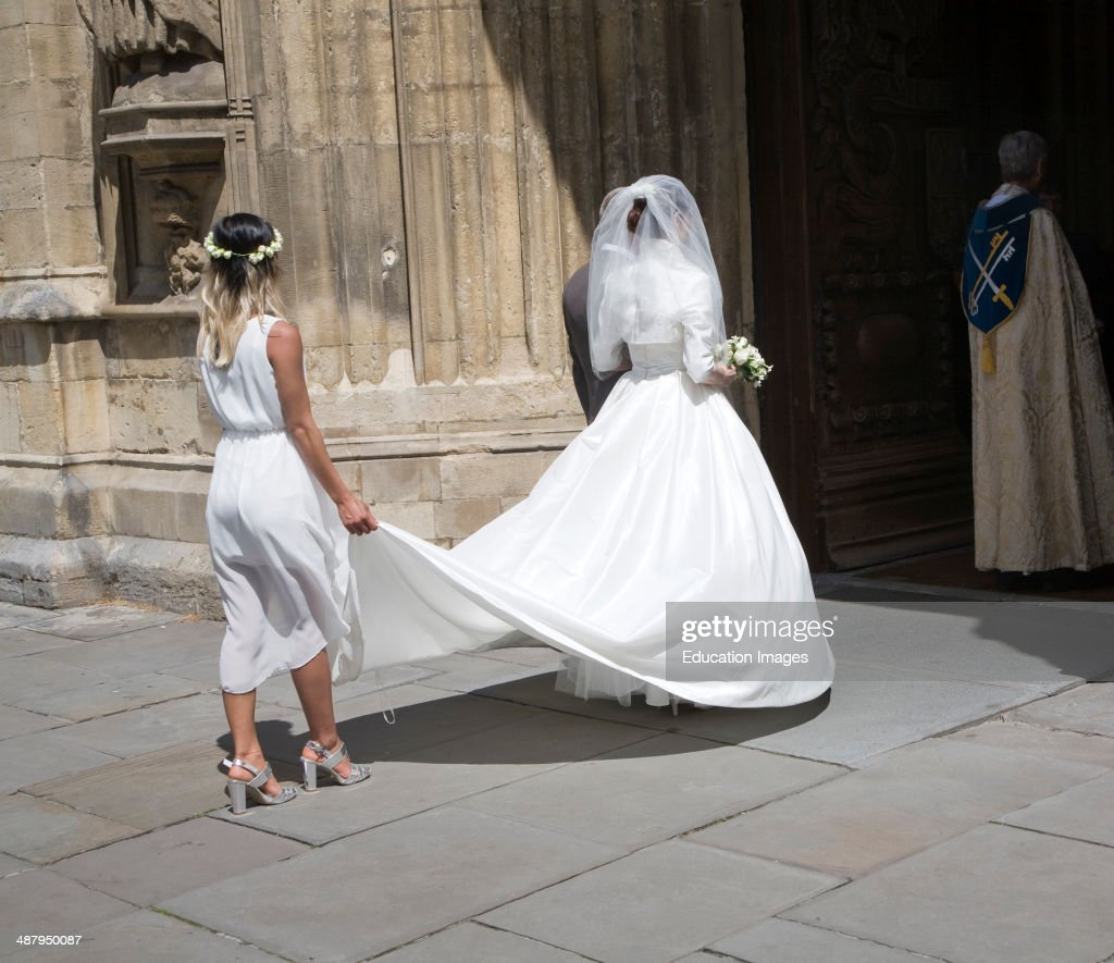 Bride in white wedding dress with bridesmaid entering Bath Abbey ...