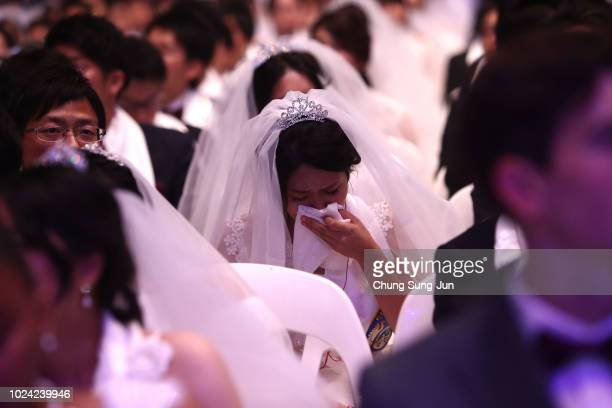 A bride weeps during an wedding ceremony of the Family Federation for World Peace and Unification commonly known as the Unification Church at...