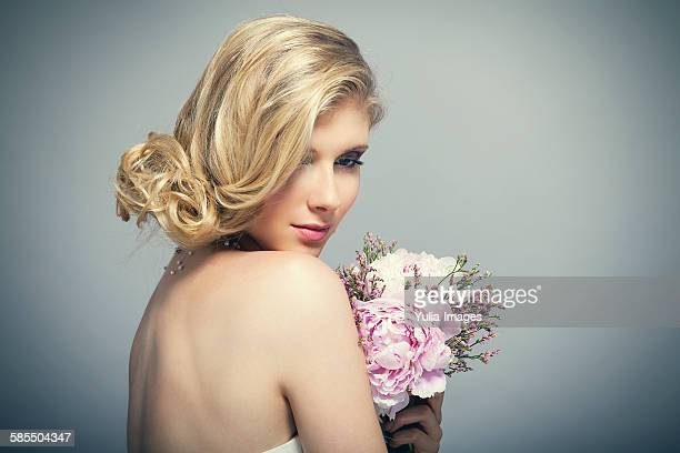 Bride with bare shoulders holding bouquet