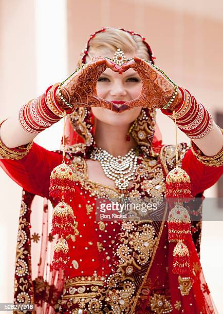 A bride with blond hair wearing a red and gold sari and jewelry holding her mehndi covered hands in a heart shape; ludhiana punjab india