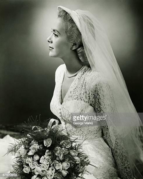 Bride with bouquet posing in studio, (B&W), portrait