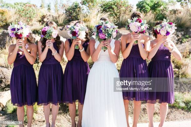 bride with bridesmaid standing with flower bouquets - bridesmaid stock pictures, royalty-free photos & images