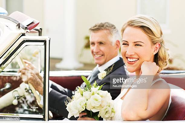 Bride With Father Looking Away While Sitting In Convertible