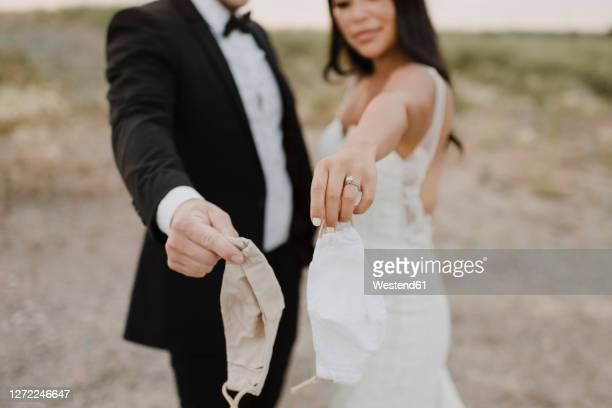 bride with groom showing protective face mask in field during covid-19 - wedding stock pictures, royalty-free photos & images