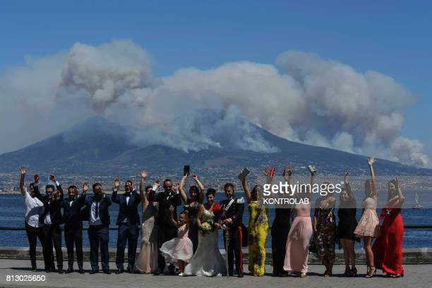 A bride with her guests in front of Vesuvius surrounded by the smoke of the fires
