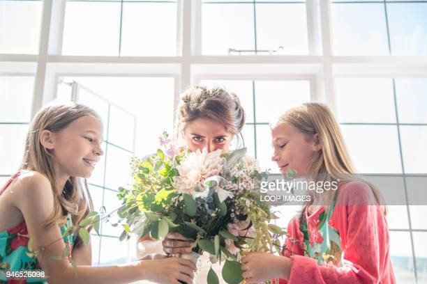 A bride with her twin bridesmaids holding a bouquet of flowers prior to her wedding