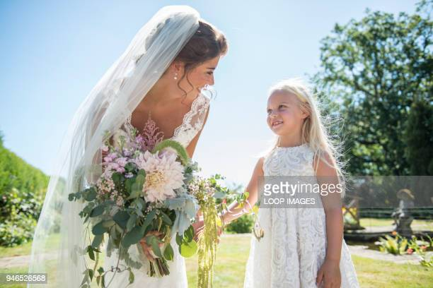 a bride with her young bridesmaid on her wedding day - bridesmaid stock pictures, royalty-free photos & images