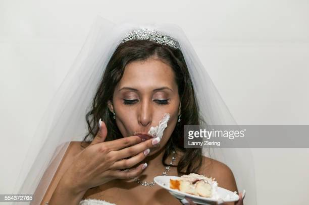 Bride with messy face eating wedding cake