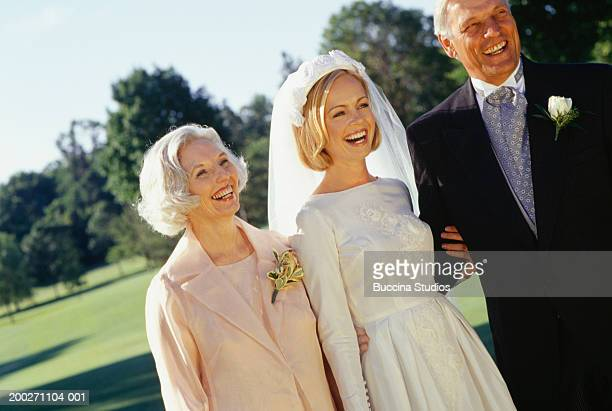 Bride with mother and father in park, portrait