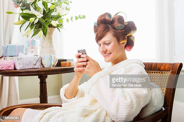 Bride with rollers in hair texting on phone.