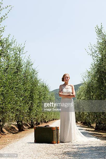 Bride with suitcase on country road, arms crossed