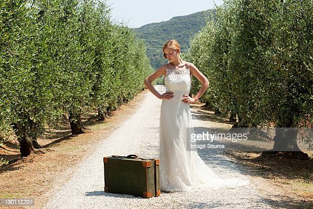 Bride with suitcase on country road, hands on hips