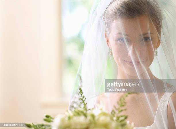 Bride with veil over face, smiling, portrait