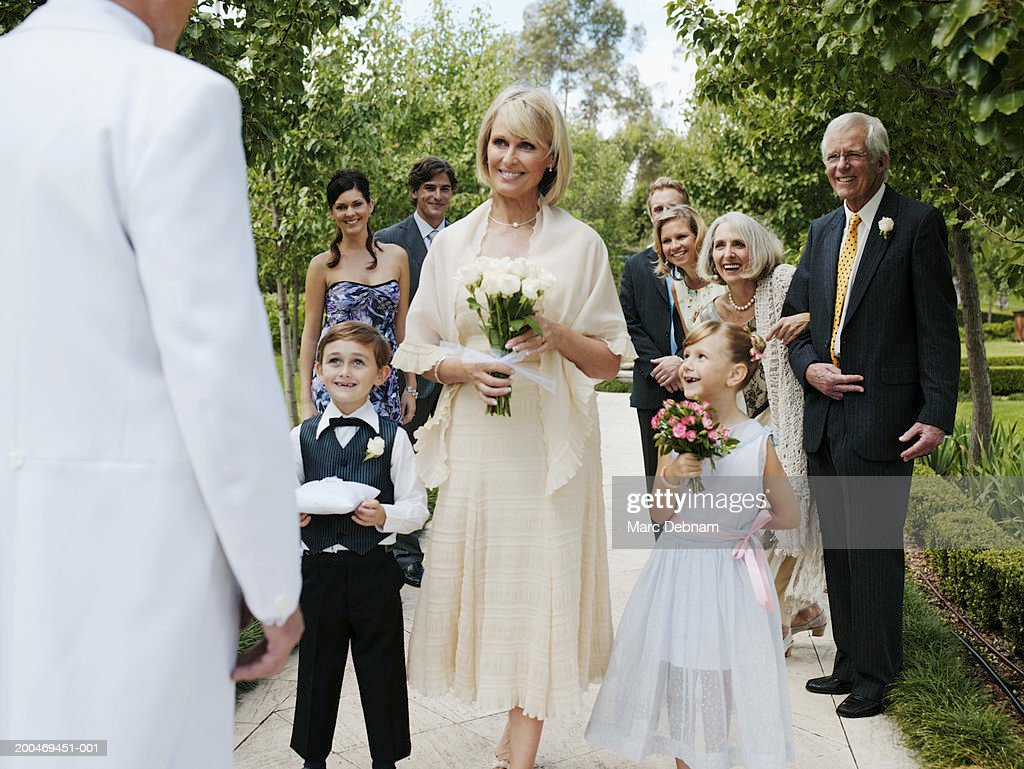 Bride with wedding guests, smiling at groom : Stock Photo