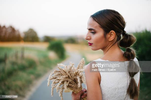 bride with wheat standing on country road - ponytail stock pictures, royalty-free photos & images