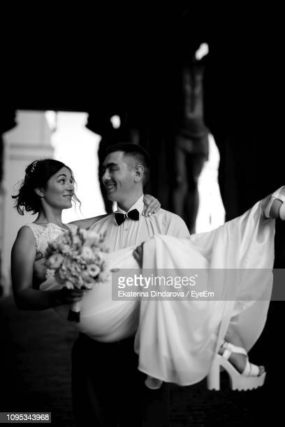 bridegroom carrying bridegroom during wedding ceremony - marriage stock pictures, royalty-free photos & images