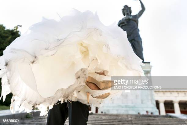 bridegroom carrying his bride in wedding dress in front of Bavaria statue in Munich
