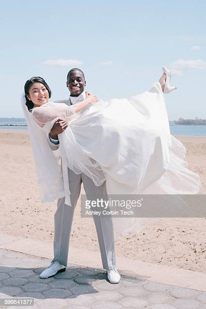 Bridegroom on beach carrying bride looking at camera smiling