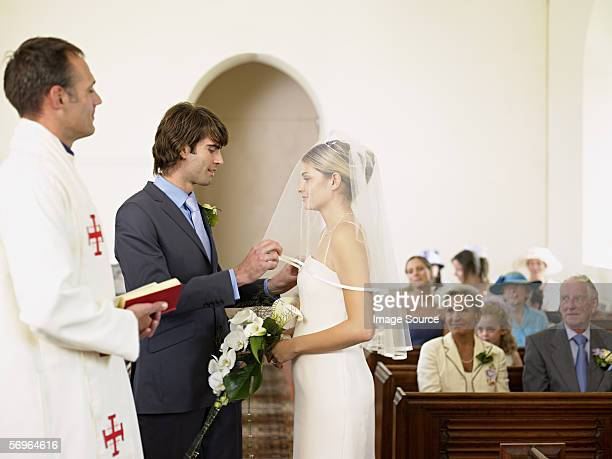 bridegroom removing brides veil - part of a series stock pictures, royalty-free photos & images
